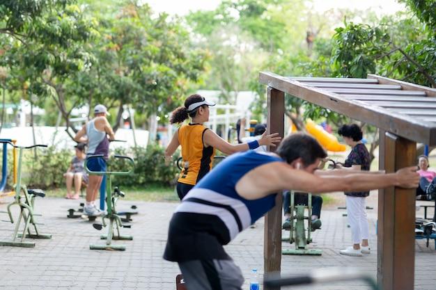 Gruppo di persone non identificato che esercitano allenamento con i pesi nel parco.