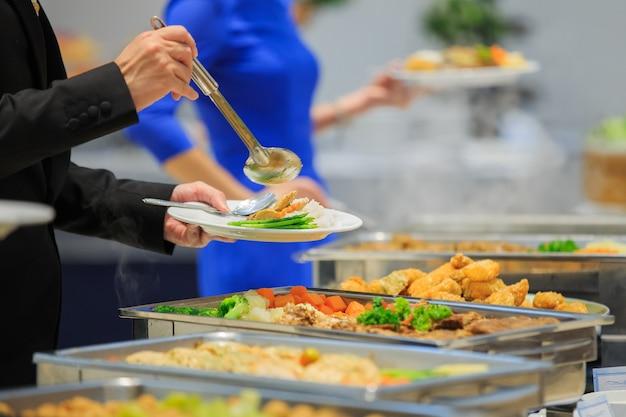 Gruppo di persone ristorazione a buffet al coperto nel ristorante di lusso con carne colorata frutta e vegetabl