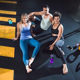 Gruppo di persone sedute sul pavimento nel fitness club