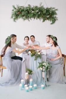 Gruppo di persone sposi, damigelle e groommen seduti al tavolo di nozze con torta nuziale, decorazioni in pino e candele in sala decorata bianca