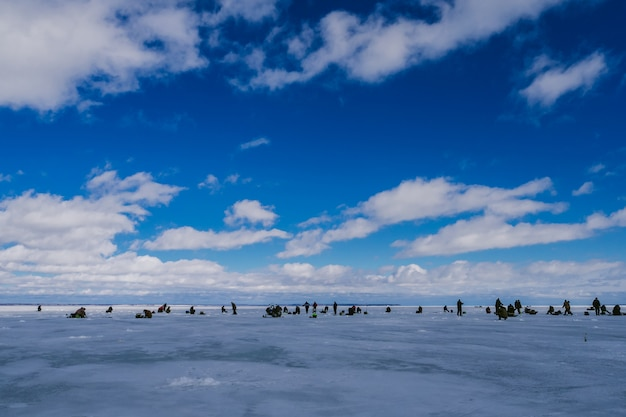 Gruppo di pescatori che pescano sullo stagno di ghiaccio