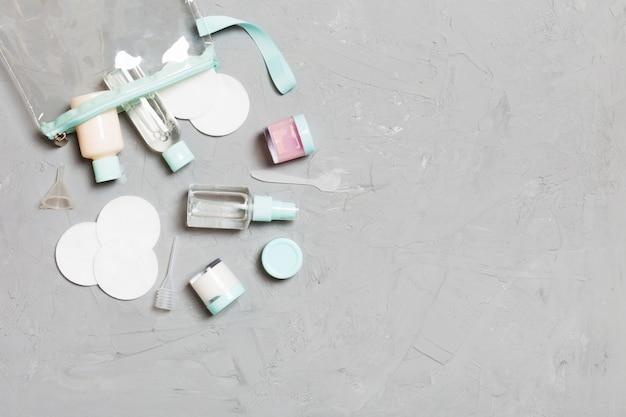 Gruppo di piccole bottiglie per viaggiare su sfondo grigio. copia spazio. composizione piatta di prodotti cosmetici. vista dall'alto di contenitori color crema con dischetti di cotone