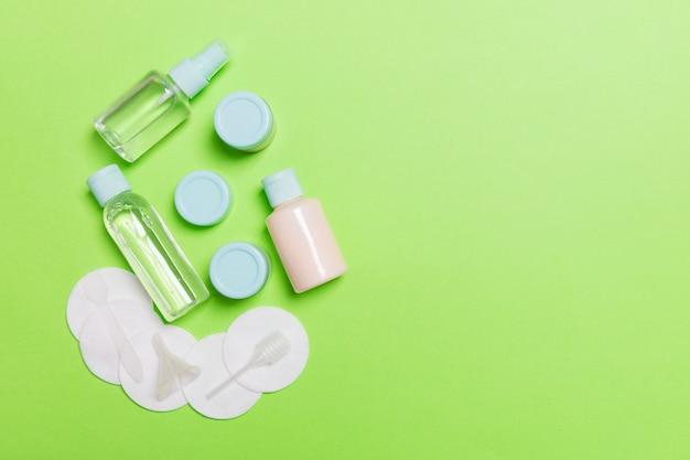 Gruppo di piccole bottiglie per viaggiare su sfondo verde. copia spazio per le tue idee. composizione piatta di prodotti cosmetici. vista dall'alto di contenitori color crema con dischetti di cotone