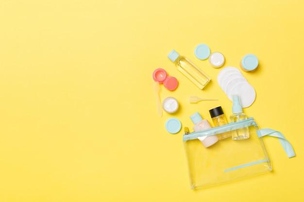 Gruppo di piccole bottiglie per viaggiare sul giallo. idee di copyspace r. composizione piatta di prodotti cosmetici. vista dall'alto di contenitori color crema con dischetti di cotone