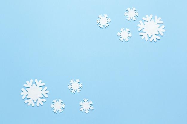 Gruppo di piccoli fiocchi di neve in feltro bianco su blu pastello, spazio di copia. orizzontale, flatlay.