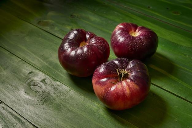 Gruppo di pomodori maturi di raf su fondo di legno verde
