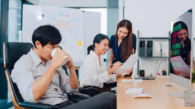 Gruppo di processo collaborativo di uomini d'affari multiculturali in abbigliamento casual intelligente che comunicano e utilizzano la tecnologia mentre lavorano insieme in ufficio creativo. il team asiatico di giovani professionisti lavora.