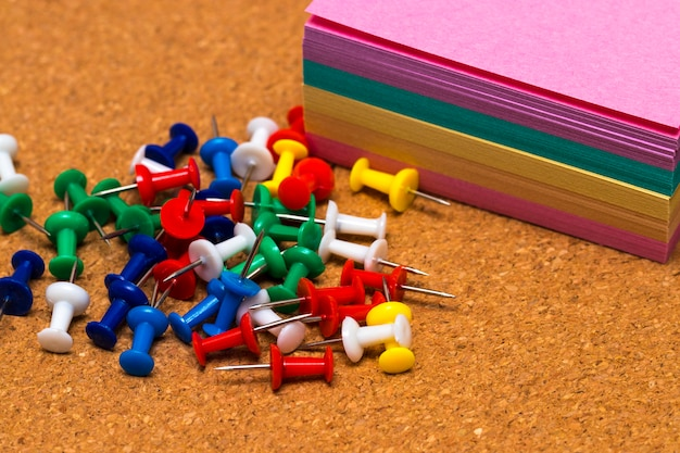 Gruppo di puntine colorate sul bordo di sughero