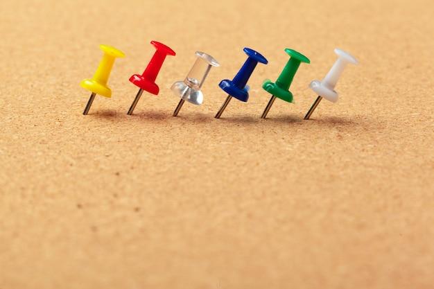 Gruppo di puntine da disegno appuntate sul pannello di sughero in una vista alta vicina di fila