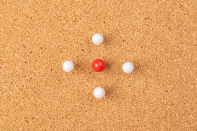 Gruppo di puntine da disegno appuntate sulla bacheca