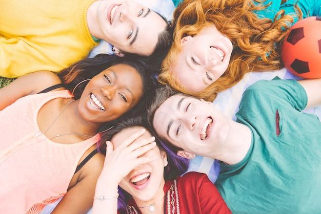 Gruppo di quattro amici che ridono ad alta voce all'aperto, condividendo il buon umore e positivo