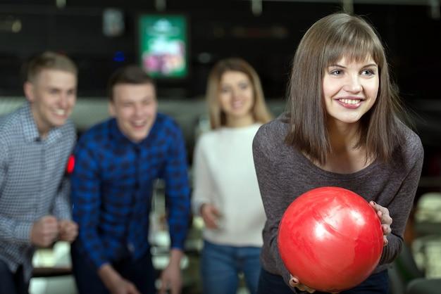 Gruppo di quattro amici in una pista da bowling divertendosi.