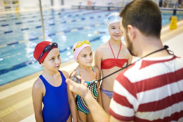 Gruppo di ragazze che ascoltano l'addestratore di nuoto