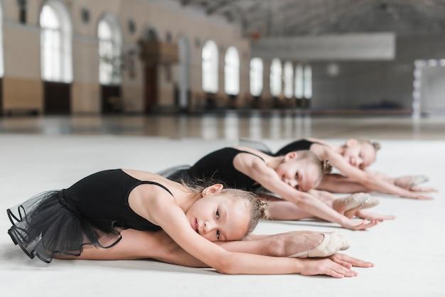 Gruppo di ragazze della ballerina che si siedono sul pavimento nello studio di ballo