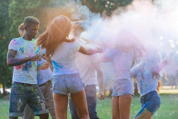 Gruppo di ragazzi che giocano con i colori al festival di holi, in un parco