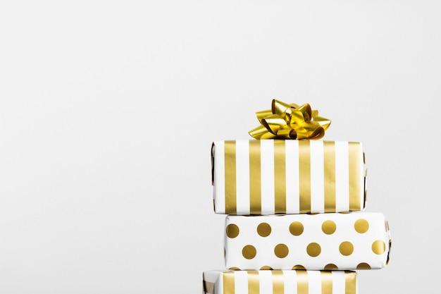 Gruppo di regali in carta bianca e oro su grigio, copia spazio