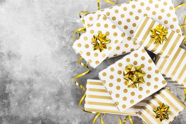 Gruppo di regali in carta bianca e oro su grigio, vista dall'alto, copia spazio