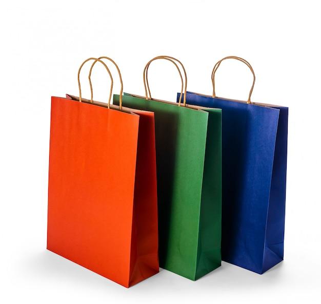 Gruppo di sacchetti della spesa di carta variopinti isolati su superficie bianca