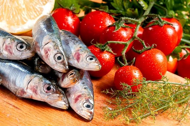 Gruppo di sardine crude su un tagliere