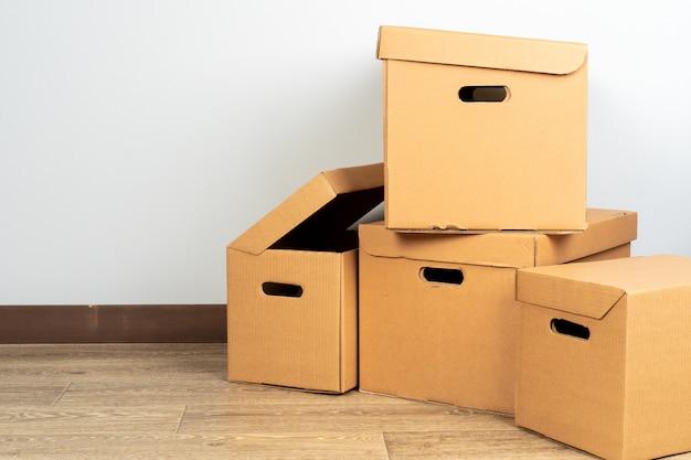 Gruppo di scatole di cartone marroni sul pavimento di legno