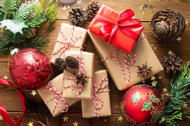 Gruppo di scatole regalo di natale avvolto in carta artigianale, rami di abete, palline rosse, pigne.