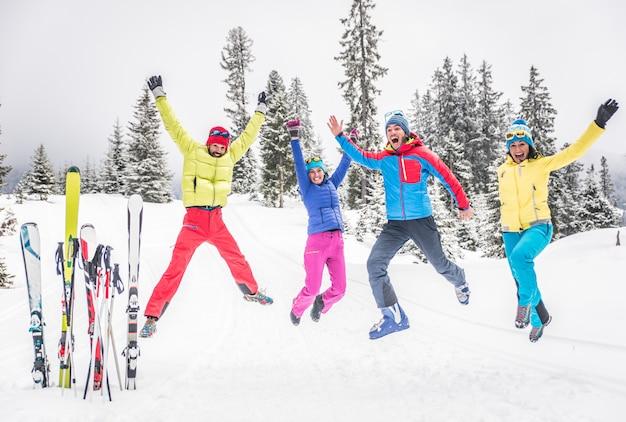 Gruppo di sciatori che saltano e si divertono