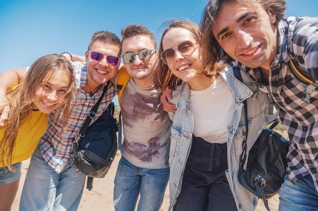 Gruppo di società di giovani graziosi abbraccianti felici, uomini e donne degli studenti su una spiaggia soleggiata, concetto di giorno di amicizia di viaggio di vacanza