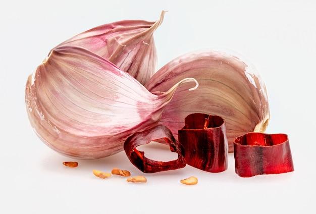 Gruppo di spicchi d'aglio rosso e porzioni di peperoncino piccante. isolato su sfondo bianco
