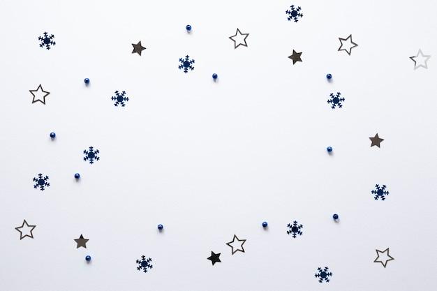 Gruppo di stelle e fiocchi di neve su sfondo bianco