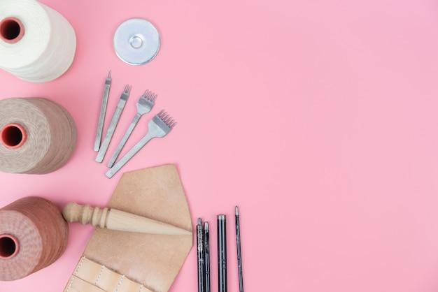 Gruppo di strumenti artigianali in pelle con corda cerata e forma pugno su sfondo rosa pastello