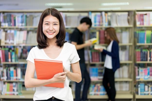 Gruppo di studenti asiatici che studiano insieme nella biblioteca all'università.