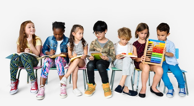 Gruppo di studenti che si siedono sulle sedie che studiano su blackground bianco