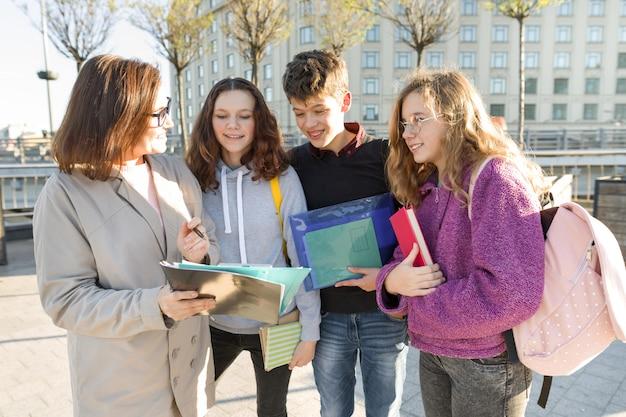 Gruppo di studenti con insegnante, adolescenti che parlano con insegnante femminile