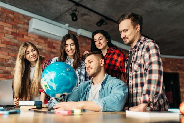 Gruppo di studenti delle scuole superiori che guardano il globo, progetto di lavoro di squadra.