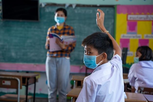 Gruppo di studenti elementari asiatici che indossano maschera protettiva per proteggersi dal covid-19, studenti in uniforme con l'insegnante che studiano insieme in aula