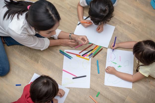 Gruppo di studenti in età prescolare e insegnante di disegno su carta in classe d'arte.