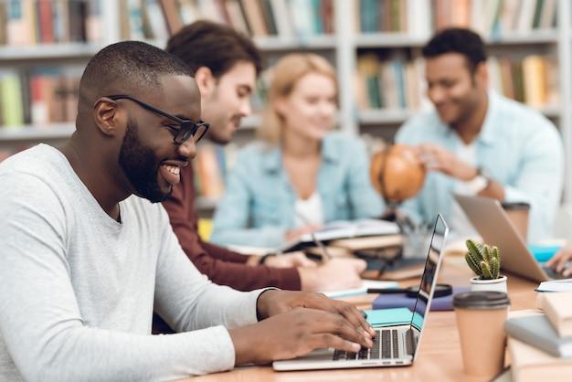 Gruppo di studenti multiculturali etnici seduti in biblioteca