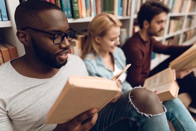 Gruppo di studenti multiculturali etnici seduti in biblioteca.