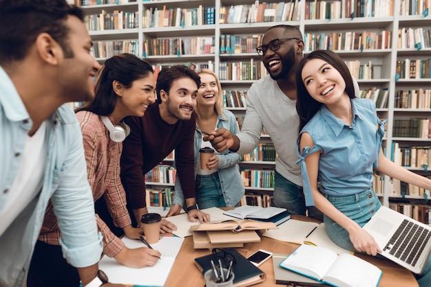 Gruppo di studenti multietnici che parlano in biblioteca.