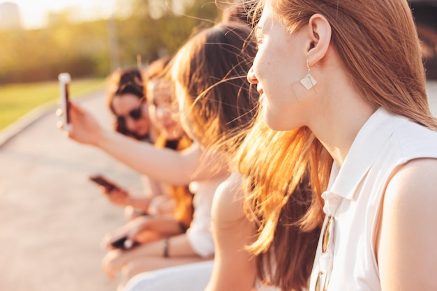 Gruppo di studenti reali amici delle giovani ragazze felici che usando cellulare alla via della città sul tramonto
