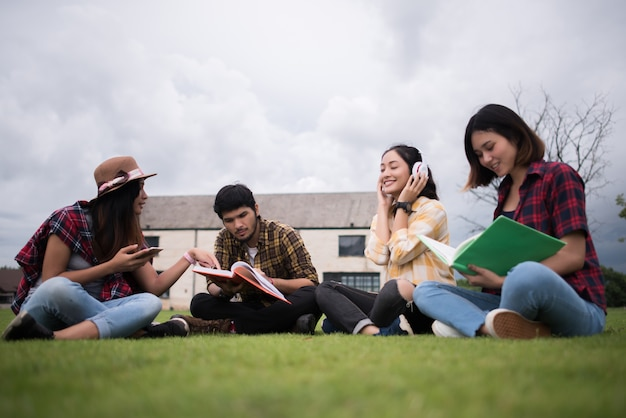 Gruppo di studenti seduti al parco dopo le lezioni. divertiti a parlare insieme.