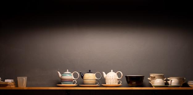 Gruppo di tazze di tè sulla parete dello scaffale di esposizione con fondo grigio scuro. luce del caffè