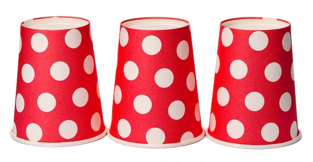 Gruppo di tazze punteggiate rosse eliminabili del cartone isolate