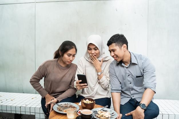 Gruppo di tre amici che utilizzano smartphone