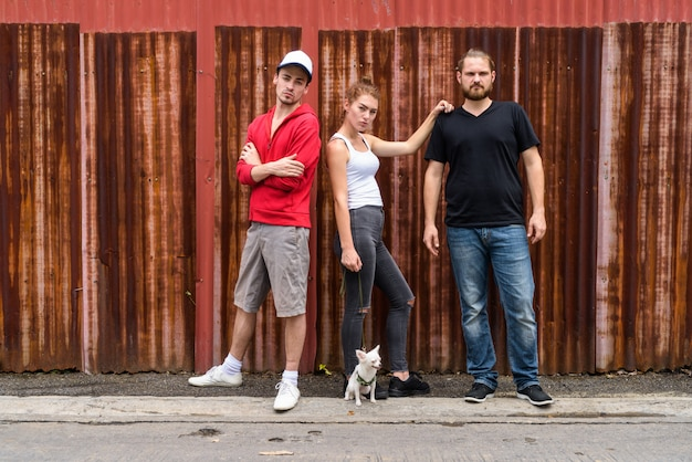 Gruppo di tre amici contro il muro di ferro arrugginito nelle strade all'aperto