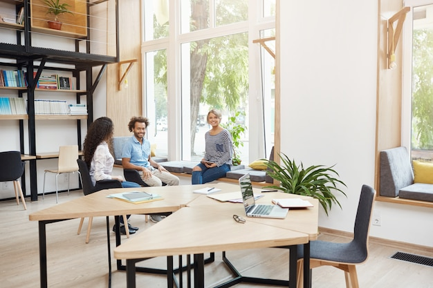Gruppo di tre giovani startup multietniche che lavorano insieme nello spazio di coworking, avendo interrotto il brainstorming. giovani che ridono, parlano, si divertono