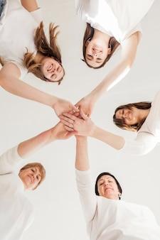 Gruppo di unità di donne che toccano le mani