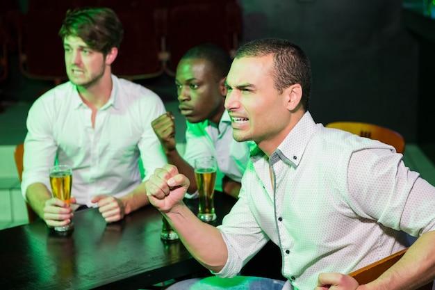 Gruppo di uomini ansiosi che guardano televisione mentre bevono birra nel bar