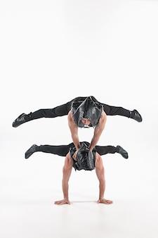 Gruppo di uomini caucasici acrobatici relativi alla ginnastica sulla posa dell'equilibrio