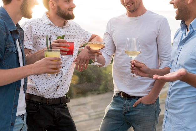 Gruppo di uomini che discutono ad una festa in terrazza